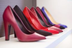High-heeled shoes standing on the shelf. Elegant shoes on the shelf close-up royalty free stock photography