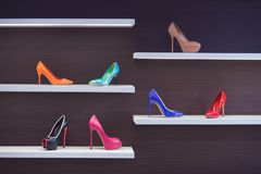 High-heeled shoes in the store. Shop window with shoes. Beautiful multi-colored high-heeled shoes. Shoes on the shelf in the store stock photography