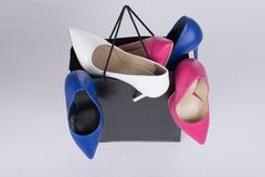 High-heeled stiletto shoe-filled shopping bag and overflowing on isolated background royalty free stock photos
