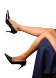 High heels. Woman relaxing her feet on a couch, wearing black high heels royalty free stock photos