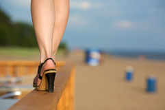 High heels on the beach. Close up of woman wearing high heels walking along narrow fence by beach Royalty Free Stock Image