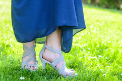 High heels and dress. Grey high heels with a blue dress standing in green grass Royalty Free Stock Photos