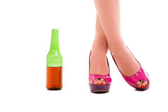 High heels with bottle of beer. High heels with glass of beer on a white background Stock Photo