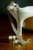 High heels and jewelery. Woman high heels, pearls, and silver on wood royalty free stock photos