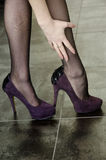 High heels and laddered stockings. Purple suede High Heel shoes and black laddered stockings royalty free stock image