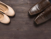 High heels and leather shoes are on wooden background Royalty Free Stock Photo