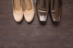 High heels and leather shoes are on wooden background Stock Photos