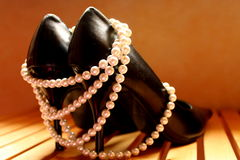 High heels. And pearl necklace as a female symbol Royalty Free Stock Photos