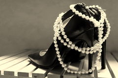 High heels. And pearl necklace as a female symbol Stock Photography