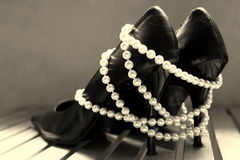 High heels. And pearl necklace as a female symbol Royalty Free Stock Image