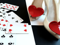 High heels with playing cards on the floor in a checkerboard. Fashion High heels with playing cards stock photos