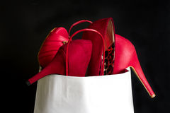 High heels red shoes in shopping bag Royalty Free Stock Photos