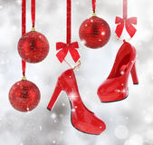 High heels shoes. And Christmas balls hanging on red ribbon stock photography