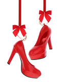 High heels shoes. Hanging on red ribbon isolated on white royalty free stock photos