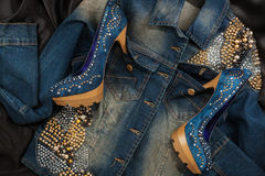 High heels of shoes are inserted into the pockets of a female denim jacket. Royalty Free Stock Photos