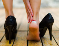 High heels sometimes hurts, little white patch in ankle. Black high heels on wooden floor Royalty Free Stock Images