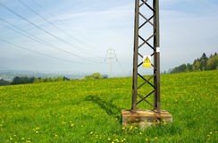 High holtage warning sign nd electric line. High holtage warning sign on metal construction. Electric power lines and pole in the background. Beatiful meadow royalty free stock photo