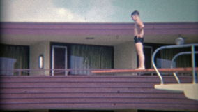 1956: High hotel diving board at the Sahara Miami Beach Hotel. MIAMI, FLORIDA. Vintage 8mm film home movie professionally cleaned and captured in 4k (3840x2160 stock video footage