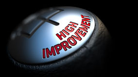 High Improvement on Black Gear Shifter. High Improvement - Red Text on Black Gear Shifter with Leather Cover. Close Up View. Selective Focus Royalty Free Stock Photos