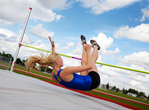 High Jump. A young, athlete clearing the bar during a high jump event, in track and field Royalty Free Stock Image