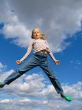 High Jump. Young girl trying to jump above the clouds Stock Photos