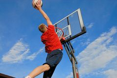 High jump. Teen jumps high and puts ball in basket Royalty Free Stock Photos