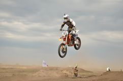 High Jump through the hill lands MX racer Royalty Free Stock Images