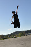 High jump on inline skates. Woman in black clothes makes high jump on inline skates Royalty Free Stock Image