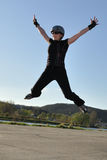High jump on inline skates. Woman in black clothes makes high jump on inline skates stock photo
