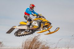 High jump of sportsman on snowmobile Stock Images