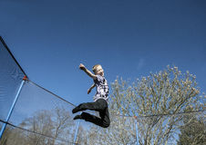 High jump on trampoline. Young boy having fun on trampoline outdoors royalty free stock photography
