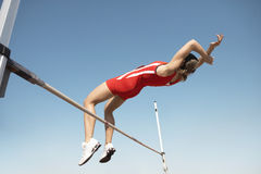 High Jumper In Midair Over Bar. Low angle view of a female high jumper in midair over bar against blue sky stock photos