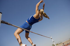 High Jumper In Midair Over Bar. Low angle view of a female high jumper in midair over bar against blue sky stock photography