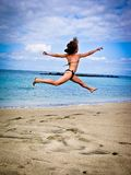 High jumping girl in a swimsuit on background of the Atlantic Ocean. High jumping girl in a swimsuit on the  beach  nearly the  Atlantic Ocean Royalty Free Stock Photography