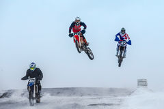 High jumps and flight riders on motorcycle at winter motocross Royalty Free Stock Image