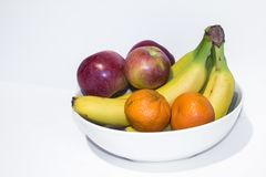 Apples, bananas, and clementines in a white bowl stock photos