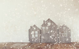 High key image of vintage wooden house decor on wooden table. retro filtered. selective focus. snow overlay Stock Photos