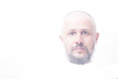 High-key portrait of bald man with grey beard. Calm looking straight Royalty Free Stock Photo