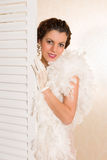 High key vintage 1920s lady. Young brunette in vintage 1920s feather boa looking from behind a folding screen in her boudoir stock photography