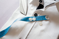 High key white shirt with measuring tape. And scissors showing fitting, design, perfect fit and tailoring Stock Image