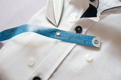 High key white shirt with measuring tape. And scissors showing fitting, design, perfect fit and tailoring Royalty Free Stock Photo