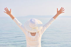 High key of woman with hands up. High key of woman wearing a hat with hands up facing the sea stock photography
