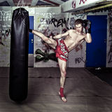High Kick. A muay thai fighter giving a high kick during a practise round with a boxing bag in an urban basement royalty free stock image