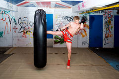 High Kick. A muay thai fighter giving a high kick during a practise round with a boxing bag in an urban basement Stock Image