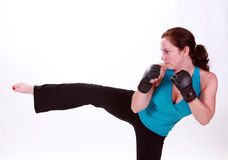 High Kick. A woman stands with mixed martial arts gloves and throwing a side kick royalty free stock image