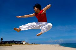 High kick. Young adult man practicing Karate on the beach. In a high kick flying through the air stock image