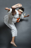 High kick. Boy in martial arts uniform doing karate Royalty Free Stock Photos