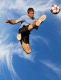 High kick. Athletic male high in the air kicking a soccer ball Stock Photo