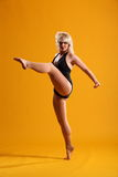 High kick dance move by beautiful blonde woman. Sexy young blonde female dancer with one leg raised, toe pointed, demonstrating dramatic high dance kick on Stock Image