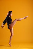 High kick dance move by beautiful woman in profile. Side on profile view of beautiful young female dancer with one leg raised, toe pointed, demonstrating stock images